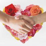 ハート型のカラフルなバラの花束と握手する男女の手