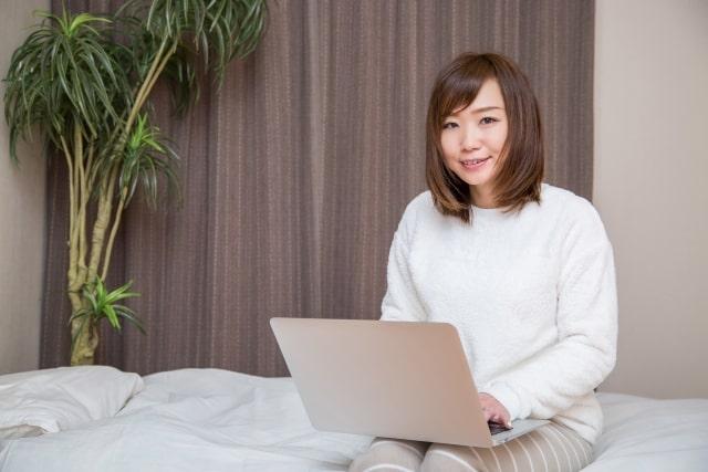 寝室でノートパソコンを使う女性