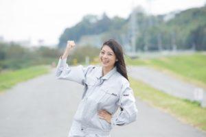 ガッツポーズの作業着姿の若い女性(屋外)