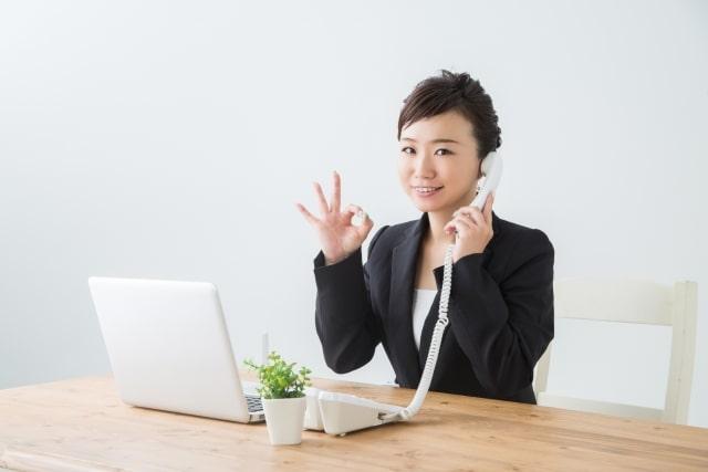 電話と笑顔のビジネスウーマン