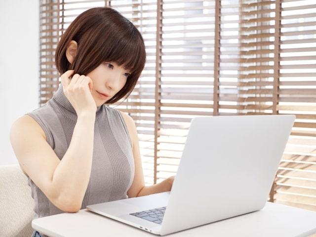 明るいリビングで悩みながらパソコンを操作する女性