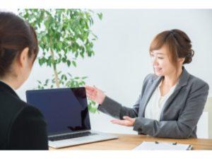 パソコン画面で明るく説明する女性
