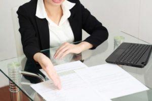 書類を使って説明するスーツ姿の女性